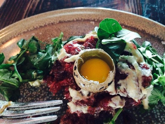a(MUSE.): New York strip steak tartare with Quail egg and arugula.