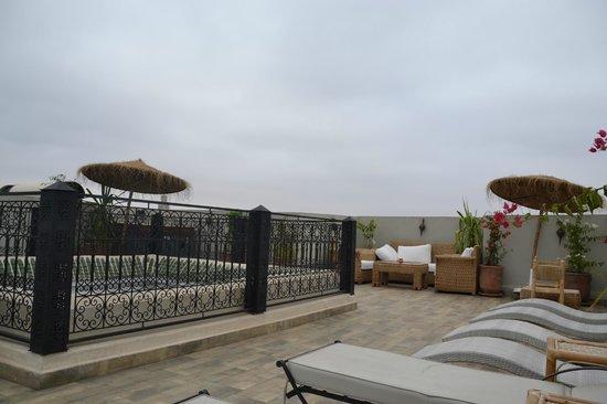 Riad Nesma: La terraza tiene mesas y sillas para desayunar, dos grupos de sofás y sillones y varias tumbonas