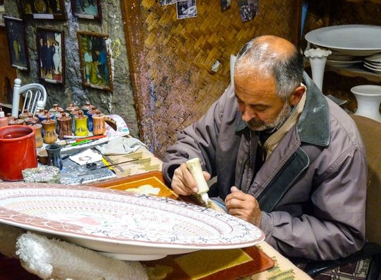 Sultans Ceramic: Multiple generations on the job - this man is painting an intricate family pattern