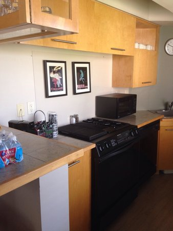 Hawthorn Suites by Wyndham Overland Park : Two seater bar with wine glasses, tumbler glasses, oven, mixing bowls below, small appliances, m