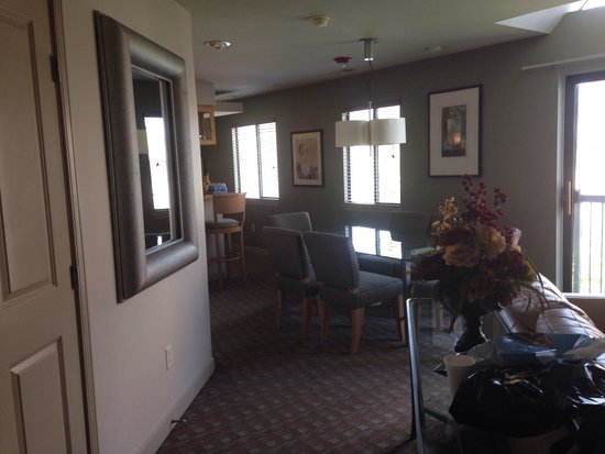 Hawthorn Suites by Wyndham Overland Park: Entry into the suite, closet on the left,  dining room table with seating for six, balcony to th