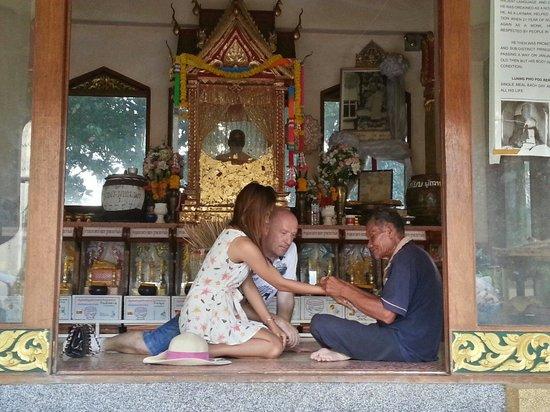 "Wat Kiri Wongkaram: Travellers met by ""uncle Da"" then he gave them holy bracelace for happy gesture."