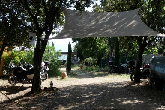 cantu di u grillu : Le stationnement devant les chambres et la terrasse au fond.