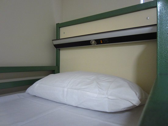 Savoy Hostel: The charging shelf and the fluffiest pillow in the world (part of a bunk set).