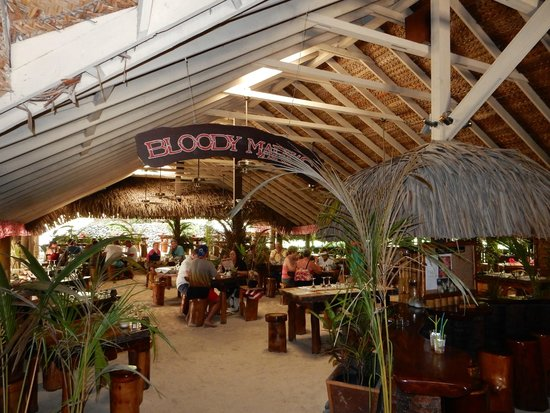 Bloody Mary's : Large dining room with sand floor and tree stump seats.