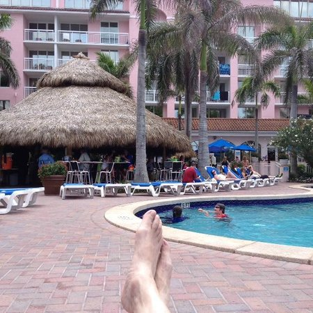 Palm Beach Shores Resort and Vacation Villas : Poolside relaxation with the Tiki bar in front andlive music behind