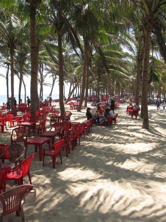 Cua Dai Beach: Seats and tables within the palm tree area
