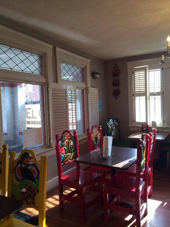 El Corcel: Dining room with charming colorful chairs.