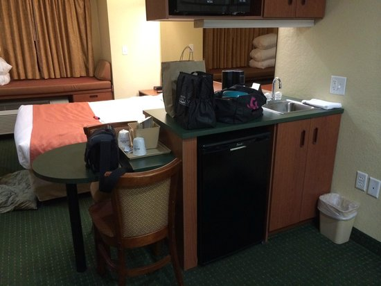 Microtel Inn & Suites by Wyndham Bushnell: View of mini kitchen area with bed behind.
