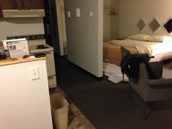 "Kennewick Suites: Bathroom is behind kitchenette, ""portals"" through wall and mirrors over bed, large sitting area."