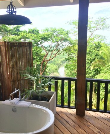 Belcampo Lodge : Looking through the floor to ceiling shower picture window to our verandah, soaker tub & Rio Gra