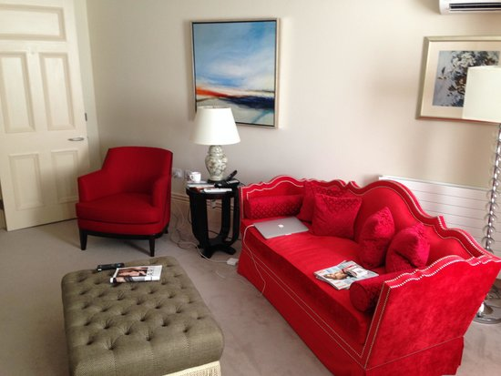 The Apartments by The Sloane Club: Basement lounge and impractical red couch