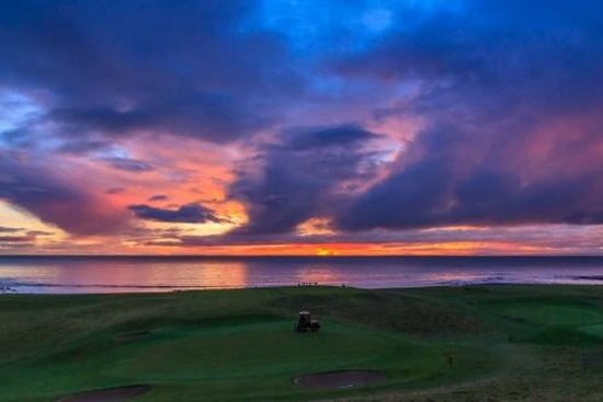 Brora Golf Course: Mowing #18, 1st tee in background at sunrise