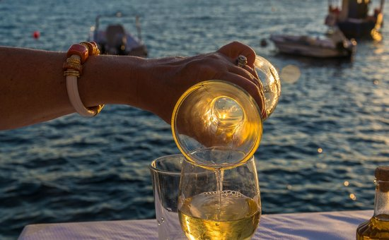 Sunset Ammoudi Taverna: Pouring wine at our water's edge table at sunset