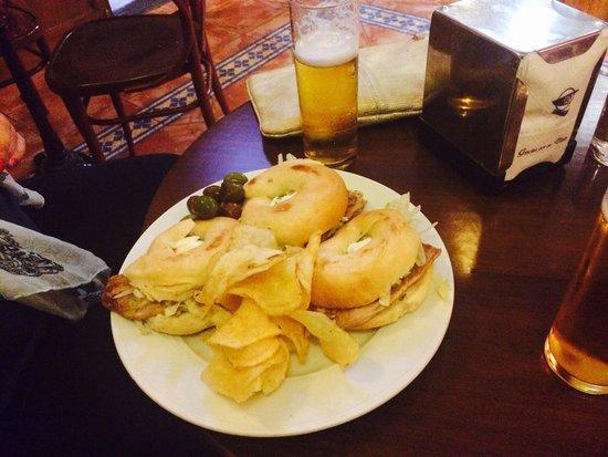 Minotauro: Tapa del día. Bagel con carne asada, salsa tártara y lechuga, más papas y olivas
