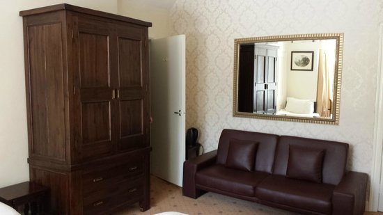 Rosery Country House Hotel: Sofa in room 8 (family room) with door to bathroom. Mirror reflected the light