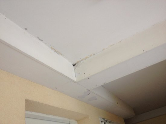 Serris, France: Peeling paint and badly finished ceiling in corridors