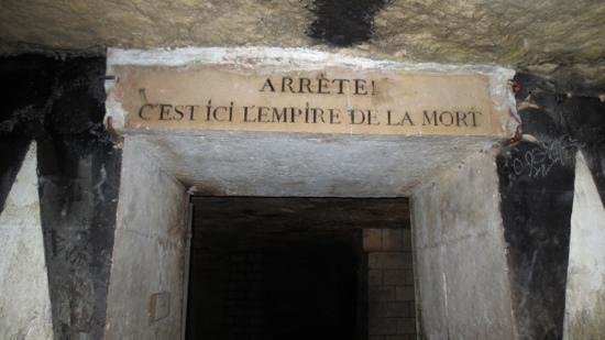 """The Catacombs of Paris: The sign reads,"""" Stop!  It is here the Empire of the Dead"""""""