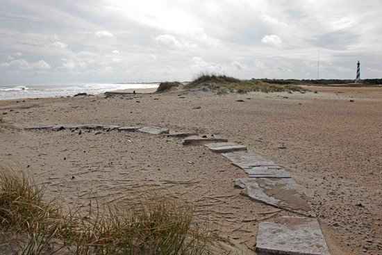 The old location of Cape Hatteras Lighthouse is marked by stones with new location in the distan