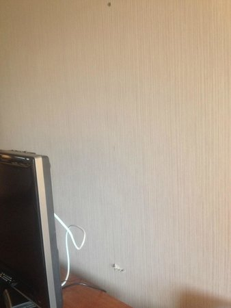 Phoenix Inn Suites South Salem: Hole gouged in wall behind TV