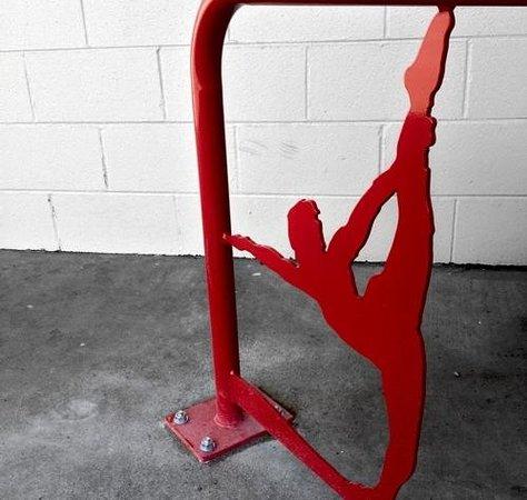Hot Power Yoga: Custom yoga-themed bike rack in front of the studio showing female silhouette in dancer pose.