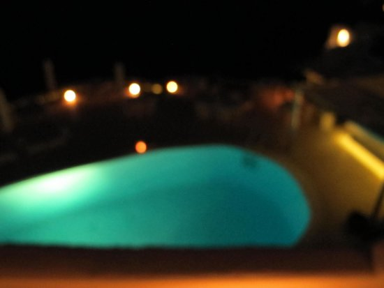 Canaves Oia Hotel: Pool and dining area at night