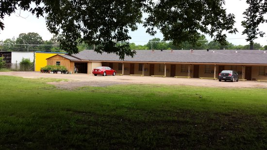 Texas Inn: PHONE: 903-742-9291   BACK OF MOTEL WITH LARGE PARKING AREA AND NICE GARDEN AND SCENERY