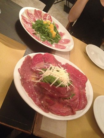 Passaguai: (Front dish) Beef Carpaccio with Rocket and Parmesan, (back dish) Smoked duck fillet with orange