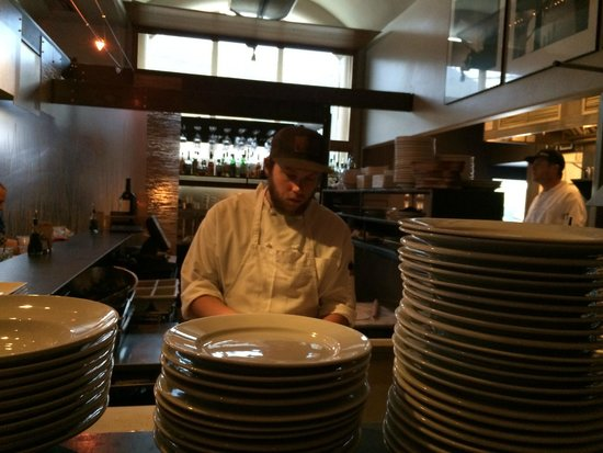 Trio An American Bistro : Chef watching!  Cooking over the open wood oven!