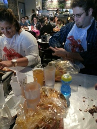 Backyard Bayou tables covered in wax paper, bibs, and your food comes out in bags