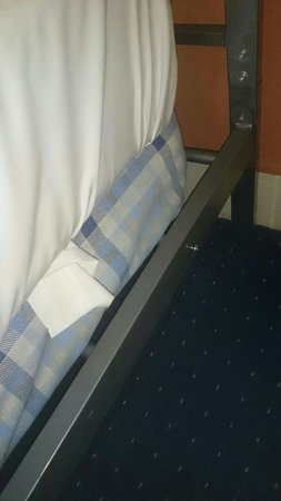 The Lonsdale Hotel : Two mattresses on the bed with screws coming lose on the side of the frame