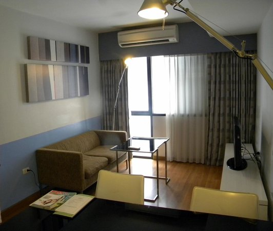 Citadines Sukhumvit 11 Bangkok: Living room with dining table, television and DVD set.