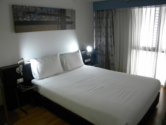 Citadines Sukhumvit 11 Bangkok: Queen sized bedroom with ironing board, desk, chair and bathroom.