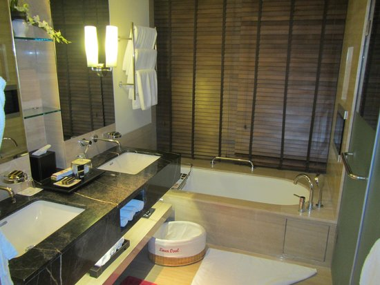 ITC Gardenia, Bengaluru: Bathroom with a small TV over the tub,  commode and shower are to the right behind separate door
