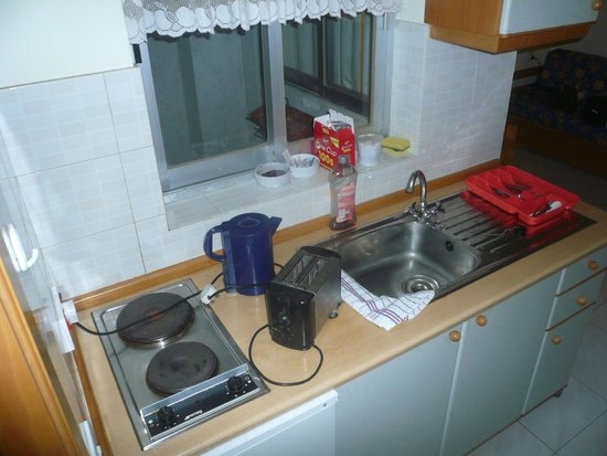 115 The Strand Hotel and Suites : Poorly equipped kitchen. Note electric lead across hotplate due to lack of space.