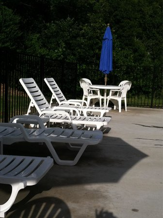 Microtel Inn & Suites by Wyndham Sylva Dillsboro Area : Sturdy Resort style lounge chairs, tables, and umbrellas.