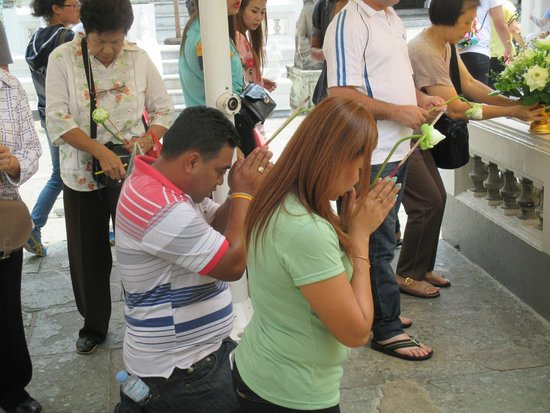 Temple of the Emerald Buddha (Wat Phra Kaew): Local citizens praying with lotus flower
