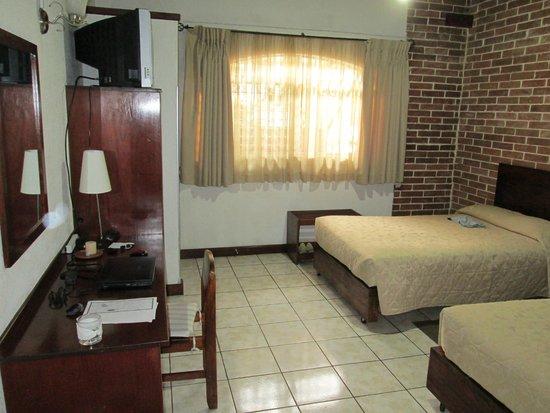 Dai Nonni Hotel : Una de las camas y ventana con vista al jardín trasero