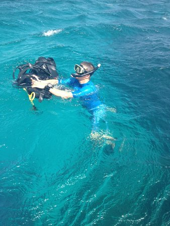 Scuba Roatan: Putting on my BCD in the water.