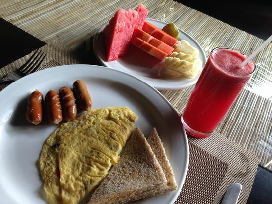 Pradha Villas: american breakfast with fruit platter and watermelon juice. You also get bacon with your eggs
