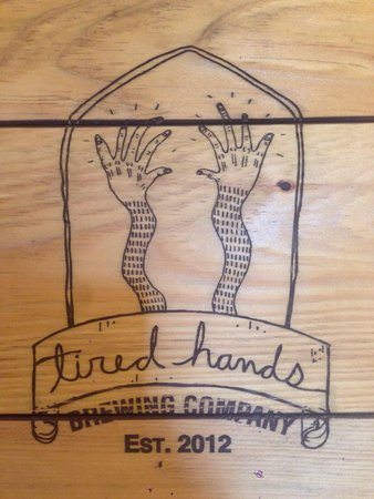 Tired Hands Brewing Company: Tired hands logo print on wood.