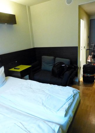 MEININGER Hotel Berlin Hauptbahnhof: Couch (futon extra bed) bedside table is desk and has small stool under it