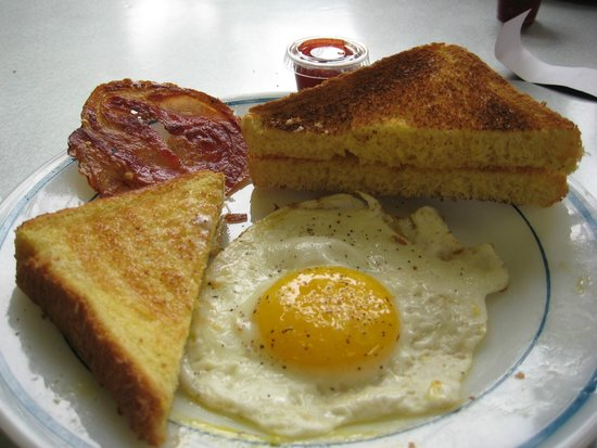 Bank Cafe: My breakfast - after I had eaten some of it. Notice the round bacon!