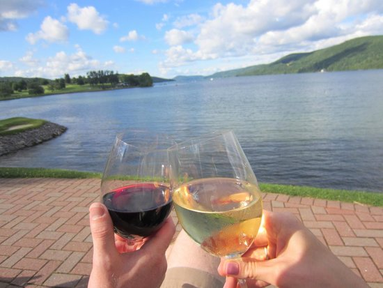 The Otesaga Resort Hotel: Enjoying a glass of wine on a bench by the lake. What a view!