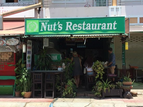 Front of the Nut's Restaurant with one long bar-like table and stools outside