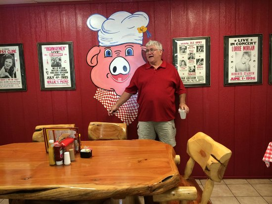 "Andy's Hog Wild Barbecue: Owner Andy standing in front of his trademark ""hawg"""
