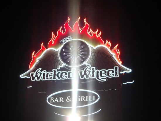 The Wicked Wheel Bar & Grill: Night time sign lit up....
