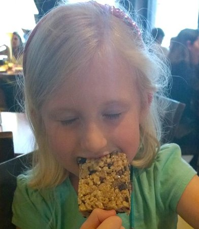 Yard House: My daughter enjoying a kids' dessert - rice krispie treat popsicle with chocolate chips