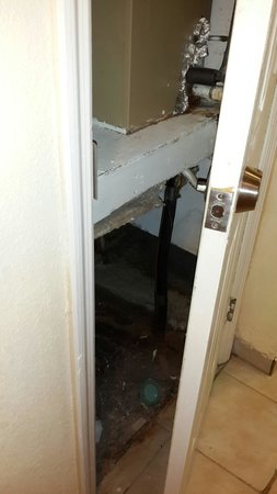 The Palms Hotel and Villas: Air handler room open IN the bathroom with thick dust, garbage and dead roaches inside