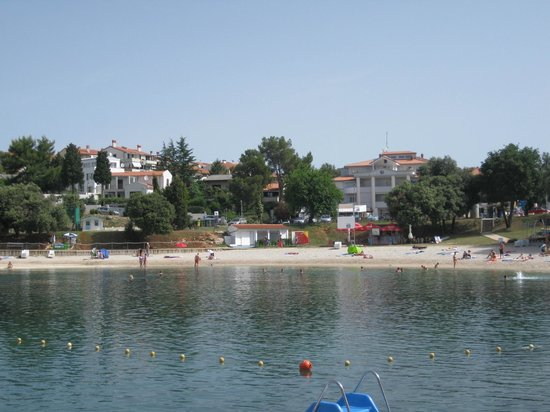 View of Beach. Villa Feniks is the tall white build above the terracotta horizontal roof